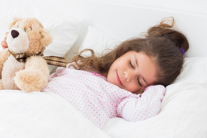 Cute girl asleep with teddy bear in bed